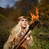 picture of torches  - Beautiful young woman outdoor on autumn day holding burning torch - JPG