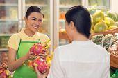 stock photo of dragon fruit  - Pretty Vietnamese saleswoman showing dragon fruits to the customer - JPG