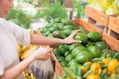 image of avocado  - Customer picking up avocadoes at the grocery store - JPG