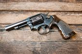 image of revolver  - black revolver gun with bullets isolated on wooden background - JPG