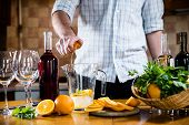image of sangria  - The man squeezes orange juice in a decanter for the preparation of sangria for home party - JPG
