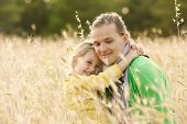 stock photo of bonding  - Caucasian mother and daughter hugging smiling and sharing a tender bonding moment amongst meadow grass. Mothers day concept. Serenity and tranquility. ** Note: Shallow depth of field - JPG