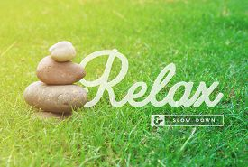 picture of motivation  - Relax and slow down motivational inspiring quote with balance zen stones and green grass background ideal for spa and wellness poster - JPG