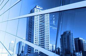 image of distort  - Buildings reflected in windows of modern office building - JPG