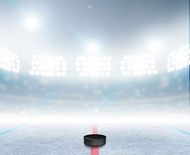 picture of illuminated  - A generic ice hockey ice rink stadium with a frozen surface and a hockey puck under illuminated floodlights - JPG