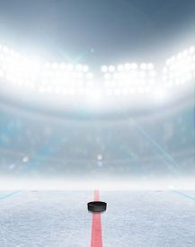 stock photo of illuminated  - A generic ice hockey ice rink stadium with a frozen surface and a hockey puck under illuminated floodlights - JPG