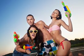 picture of pistols  - Group of young joyful young people playing and posing with water pistols on the beach  - JPG