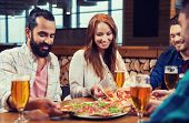 leisure, food and drinks, people and holidays concept - smiling friends eating pizza and drinking be poster