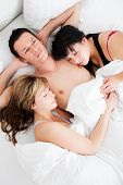 stock photo of threesome  - Successful man lying with two girls in bed - JPG