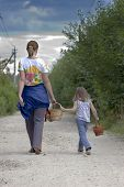 picture of family vacations  - Mother and daughter are walking far away on rural road in cloudy summer day - JPG
