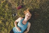 Relaxing Outdoor. Young Woman Relaxing In The Park After Running poster