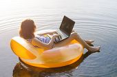 Freelancer Works On A Laptop Sitting In An Inflatable Ring In The Water, Free Space. Business Woman poster