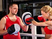 Boxing workout woman in fitness class ring. Sport box exercise two people. Man trainer holding sport poster