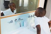 High angle view of boy clenching teeth while looking at mirror in domestic bathroom poster