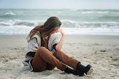 Alone sad woman sitting on a sea beach poster