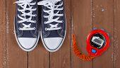 Clothes, Shoes And Sport - Top View Fragment Closeup Pair Blue Gumshoes And Red Stopwatch On A Woode poster
