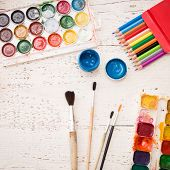 Closeup Of Creative Space, Watercolors, A Brush And Some Art Stuff On A White Wooden Table. Creative poster