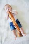 Six Months Old Baby Girl Eating Traditional French Bread (baguette). Introducing Solids To Infant Ki poster