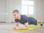 Portrait Of Sporty Smile Man Doing Planking Exercise On Mat In Room poster