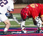 Two High School Lacross Players Are Fighting For The Ball During A Face Off And One Has The Ball Tra poster
