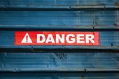 Danger Sign On Red Tape Over Grungy Blue Metal Wall, Close-up poster