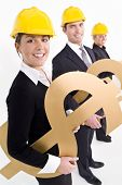 stock photo of industrial safety  - Conceptual studio shot of business executives holding various large golden currency symbols and wearing hard hats - JPG