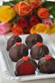 stock photo of red velvet cake  - Red Velvet Cake Pops with roses in the background - JPG