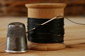 Sewing still life of antique thimble with wooden spool of thread and vintage needle on wood backgro