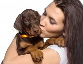 Brunette girl kissing her doberman puppy isolated on white background