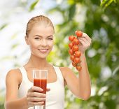 gitness and diet concept - young woman holding glass of juice and tomatoes