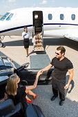 stock photo of bodyguard  - High angle view of bodyguard assisting elegant woman stepping out of car at airport terminal - JPG