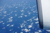 aerial view of blue sky with clouds from jet flight. Focus on clouds