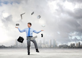 stock photo of juggling  - Young businessman juggling with business items against urban scene - JPG