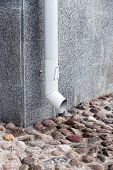 image of downspouts  - Wall of building with white metall downspout and pavement