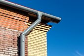 stock photo of gutter  - Newly installed modern gutter system with drainpipe - JPG