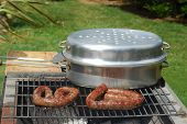 stock photo of braai  - A typical and traditional South African barbecue with wurst and Braai pot in the garden outdoors - JPG