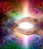 stock photo of kundalini  - Male healer with outstretched healing hands and shaft of white light light on a rainbow colored web formation background - JPG