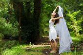 picture of barefoot  - Beautiful barefoot woman in a stylish white dress pose in a forest  of lush green trees - JPG