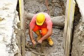 stock photo of wet pants  - construction worker with yellow boots in the excavation of a roadworks for the laying of optical fibre  - JPG