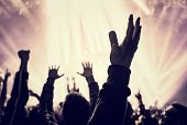 picture of excite  - Grunge style photo of silhouette of people hands raised up on musical concert - JPG