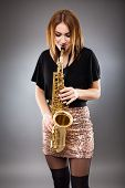 image of saxophone player  - Beautiful blond woman saxophone player studio closeup shot - JPG