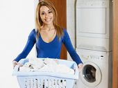 stock photo of washing machine  - woman holding basket of laundry and looking at camera - JPG