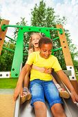 stock photo of chute  - Boy start to slide on chute and girl sit behind and hugs him with arms excited with open mouth - JPG