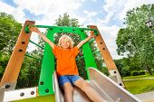 stock photo of chute  - Boy slides on playground chute with hands up - JPG