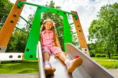 pic of chute  - Pretty small girl on playground chute sitting and smiling in the park - JPG
