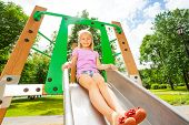 picture of chute  - Charming girl on playground chute ready to slide and holding the sides of it - JPG