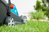 stock photo of grass-cutter  - Lawn mower on a green meadow. Gardening equipment
