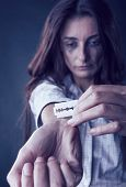 pic of mutilated  - Young woman cuts veins on a hand on a dark background. Focus on hand