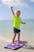 picture of boogie board  - A happy young child is raising his fist in the air as a cheer as he stands up to surf on a boogie board in the ocean on a vacation day at the beach - JPG