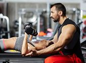 stock photo of personal assistant  - Personal fitness trainer assisting a young woman in the gym at a workout - JPG